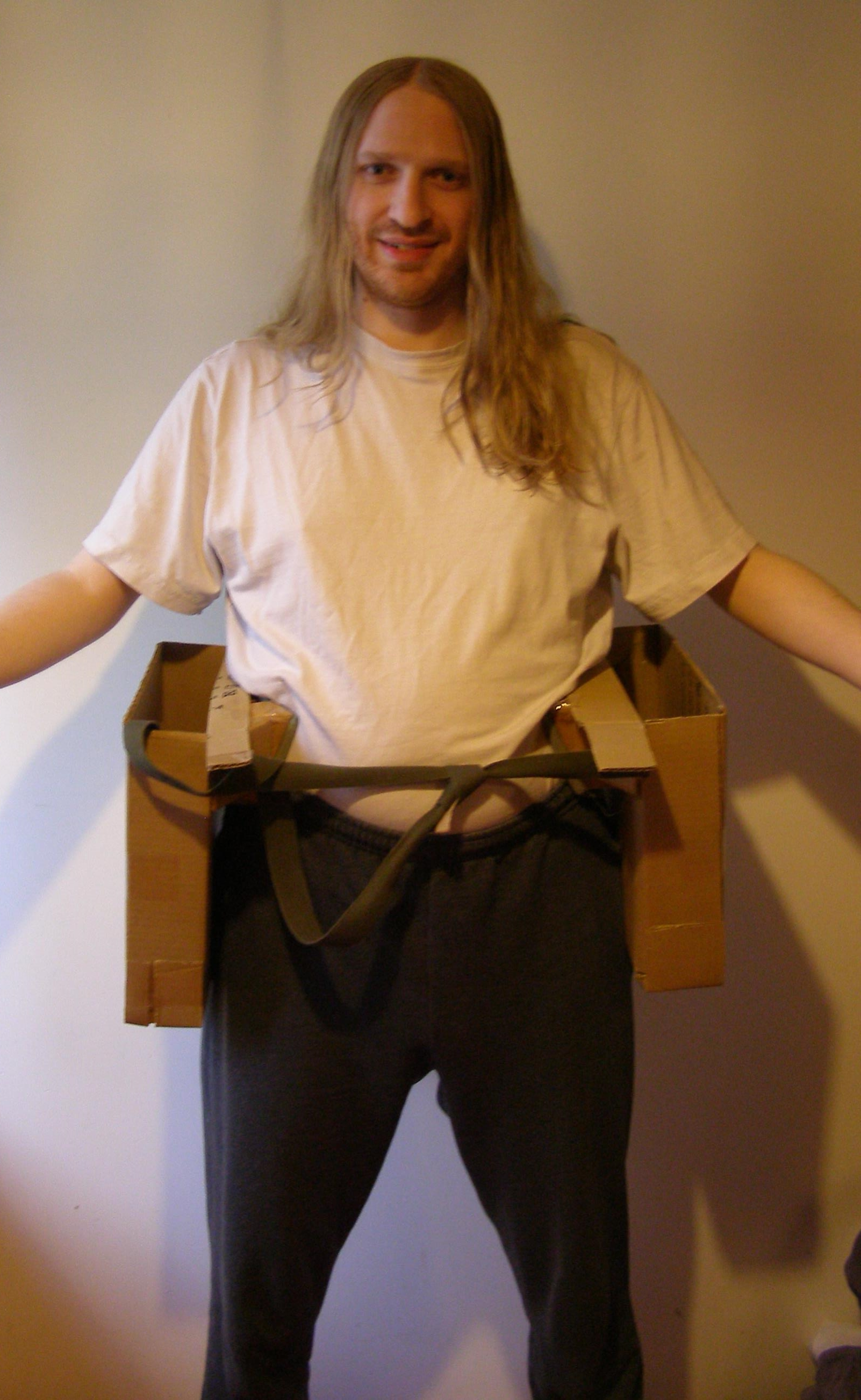 [Photo: Me, wearing Saddlebags 2.1 around my hips. They are two cardboard boxes at my sides, connected by a strap.]